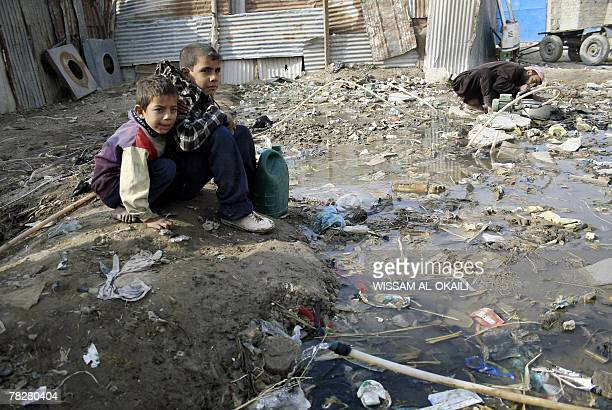 Iraqi boys drink water from a water pipe crossing an uncovered sewage canal at the area of Fdailiyah southeast of Baghdad 06 December 2007 Many of...