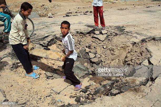 Iraqi boys lift wreckage from a crater created from an improvised explosive device detonated during fierce clashes between Shiite fighters and Iraqi...