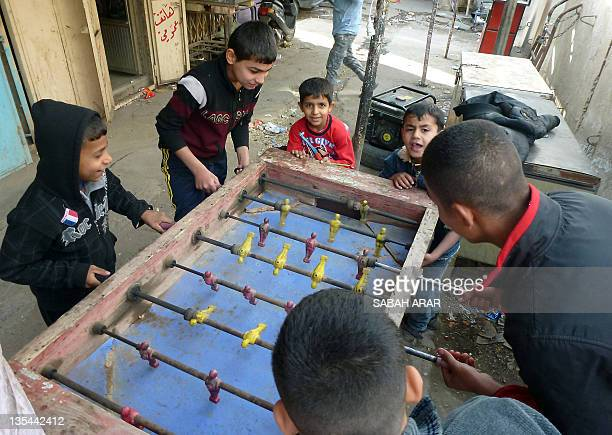 Iraqi boys play table football at Shorja market in Baghdad on December 10 2011 The withdrawal of US troops from Iraq more than eight years after the...