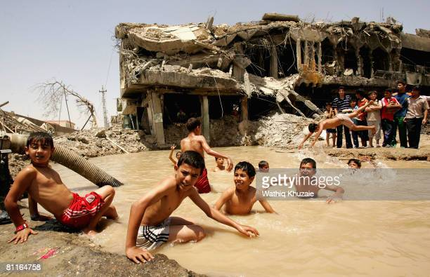 Iraqi boys swim in a pond caused by an explosion from recent fighting on May 20 2008 in the Shiite district of Sadr City in Baghdad Iraq Iraqi...