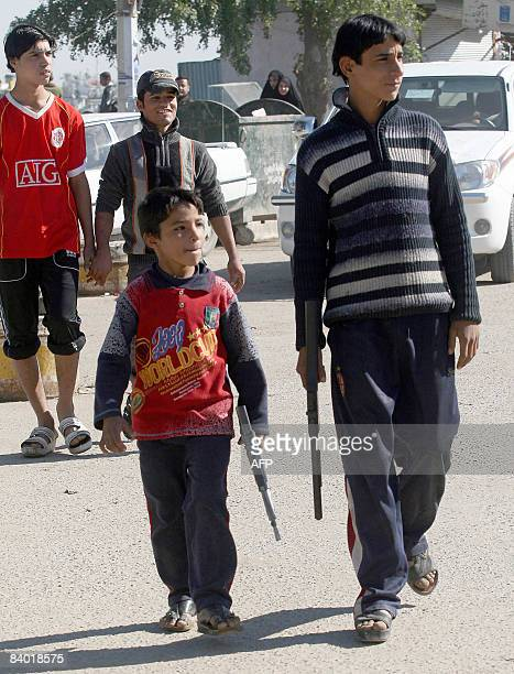 Iraqi boys walk along a street carying plastic toy rifles in the southern city of Basra some 550 kms from the capital Baghdad on December 13 2008 The...