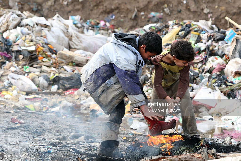 Iraqi boys warm themselves over a fire in a garbage dump on the outskirts of Baghdad's impoverished district of Sadr City, January 30, 2013. The UN has said Iraq is one of the countries in the Arab world most vulnerable to climate change, pointing to 'a higher frequency and intensity of extreme weather events and rising environmental degradation throughout the country.'