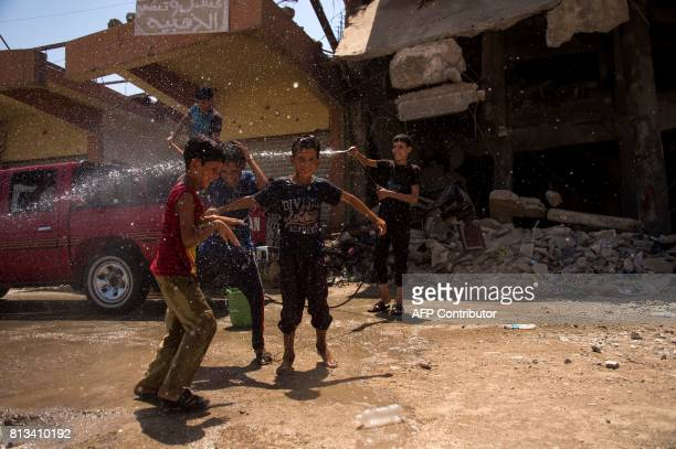 TOPSHOT Iraqi boys wash a vehicle in west Mosul on July 12 a few days after the government's announcement of the 'liberation' of the embattled city...