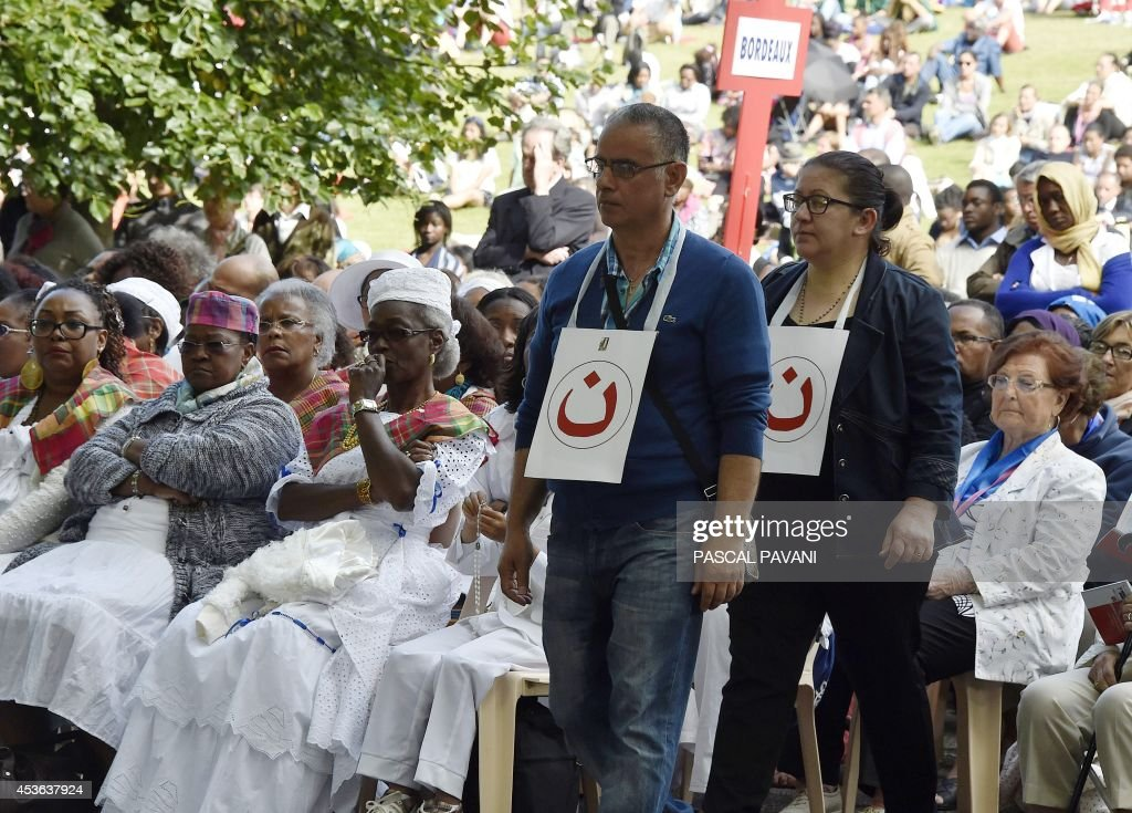 Iraqi catholic pilgrims with a sign attached around their necks showing the 'Nazarene' (a symbol painted on Christian's houses in Iraq to locate them) pray during the feast of the Assumption on August 15, 2014 in the sanctuary of Our Lady in the French Southwestern pilgrimage city of Lourdes.
