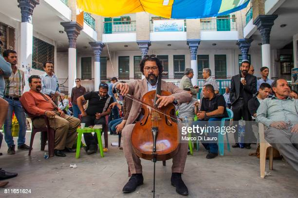Iraqi cellist and conductor Karim Wasfi 43yearsold is seen playing his cello in the Mutanabbi street on April 24 2015 in Baghdad Iraq'nKarim was born...