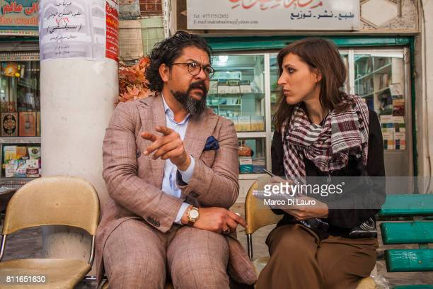 Iraqi cellist and conductor Karim Wasfi 43yearsold is seen talking to Theresa Breuer from Stern in the Mutanabbi street on April 24 2015 in Baghdad...