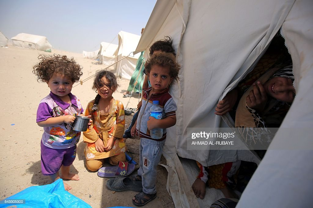 Iraqi children displaced from the city of Fallujah gather next to a tent at a newly opened camp where hundreds of displaced Iraqis are taking shelter in Amriyat al-Fallujah on June 27, 2016, south of Fallujah. Iraqi forces on June 26 wrapped up operations in Fallujah and declared the area free of jihadists from the Islamic State (IS) group after a month-long operation. The government said the destruction caused by the fighting was limited and vowed to do its utmost to allow the tens of thousands of displaced civilians to return to their homes. RUBAYE
