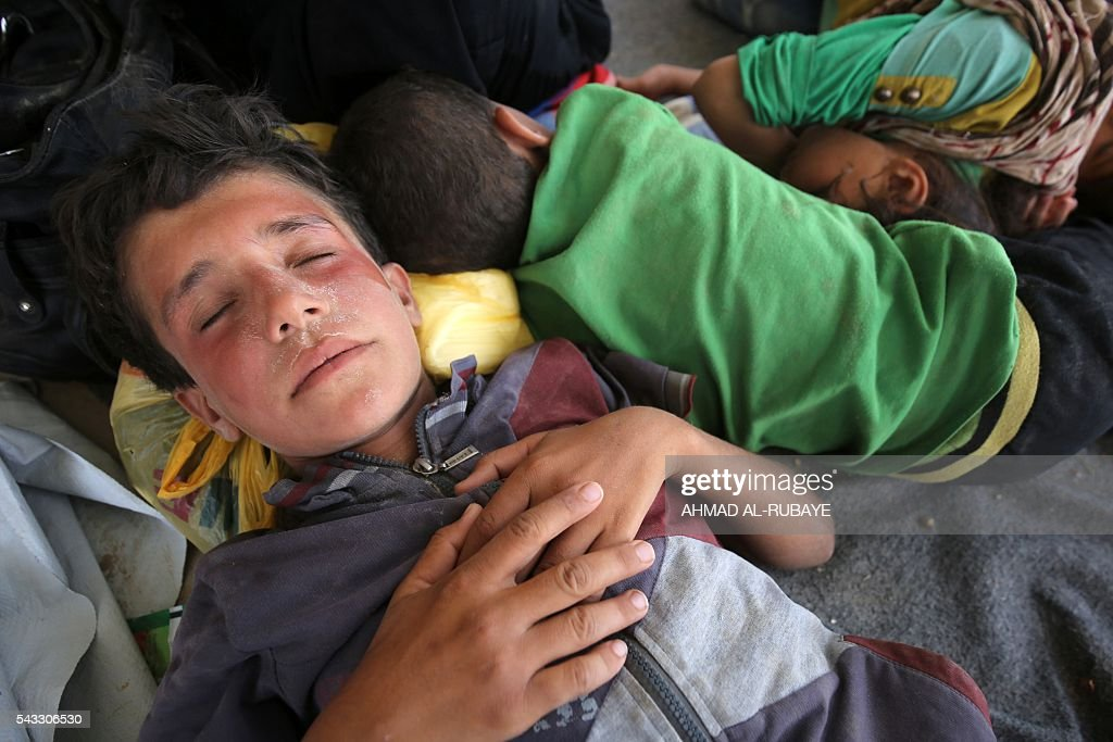 Iraqi children displaced from the city of Fallujah sleep at a newly opened camp where hundreds of displaced Iraqis are taking shelter in Amriyat al-Fallujah on June 27, 2016, south of Fallujah. Iraqi forces on June 26 wrapped up operations in Fallujah and declared the area free of jihadists from the Islamic State (IS) group after a month-long operation. The government said the destruction caused by the fighting was limited and vowed to do its utmost to allow the tens of thousands of displaced civilians to return to their homes. RUBAYE