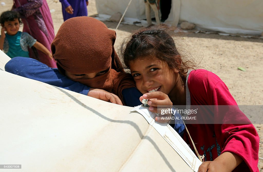 Iraqi children displaced from the city of Fallujah smile next to a tent at a newly opened camp where hundreds of displaced Iraqis are taking shelter in Amriyat al-Fallujah on June 27, 2016, south of Fallujah. Iraqi forces on June 26 wrapped up operations in Fallujah and declared the area free of jihadists from the Islamic State (IS) group after a month-long operation. The government said the destruction caused by the fighting was limited and vowed to do its utmost to allow the tens of thousands of displaced civilians to return to their homes. RUBAYE