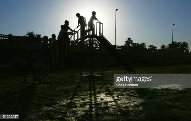 Iraqi children file up the stairs of a slide on a new playground July 2 2004 in Baghdad Iraq The playground which opened today was funded by the US...
