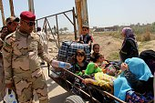 Iraqi children fled the Iraqi city of Ramadi seized by Daesh militants are carried by trailer as an Iraqi army soldier passes water them after they...