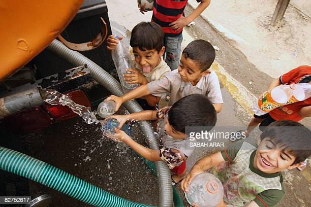 Iraqi children gather around a cistern delivering fresh drinking water to the Karada neighborhood of Baghdad on September 10 2008 The central Iraqi...