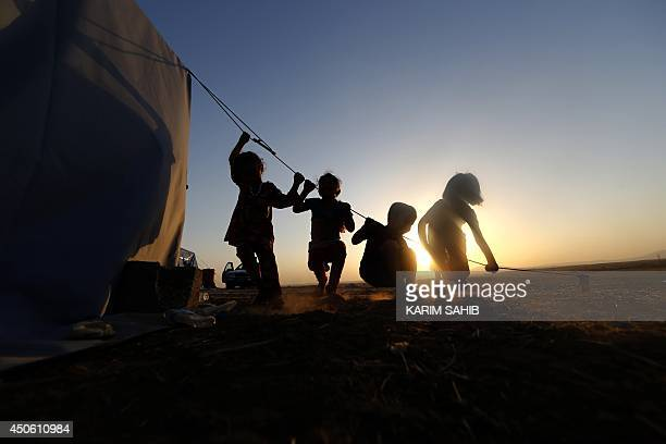 Iraqi children play on the guideline of a tent setup in a temporary camp set up to house civilians fleeing violence in Iraq's northern Nineveh...