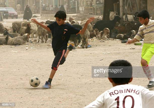 Iraqi children play soccer on the dusty streets of the Sadr City district of eastern Baghdad following several months of fighting between Mahdi Army...