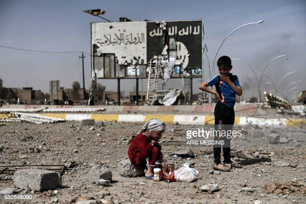 TOPSHOT Iraqi children sit amidst the rubble of a street in Mosul's Nablus neighbourhood infront of a billboard bearing the logo of the Islamic State...
