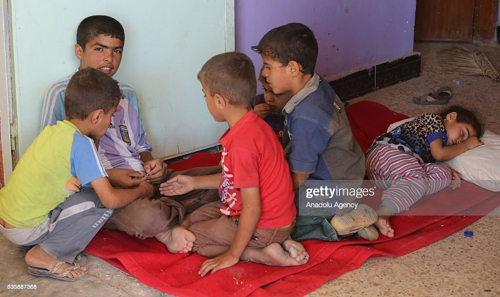 Iraqi children sit on a blanket as they leave their home in Fallujah town due to conflicts between Daesh and security forces in Anbar, Iraq on May 30, 2016. Some of the families who left their home are placed in a school in Karma Town, west of Anbar city.