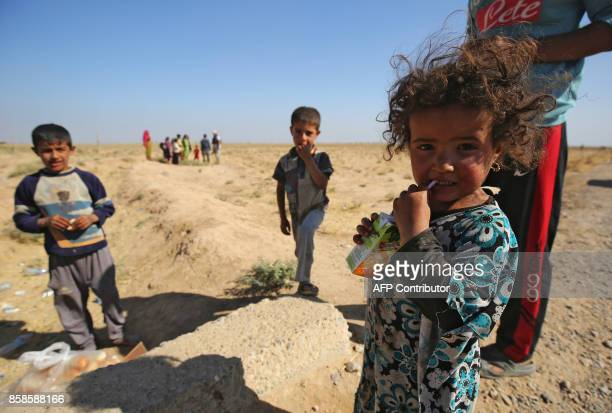 Iraqi children stand on the side of the road as they receive food from a charity in a village on the outskirts of Hawija on October 6 a day after...