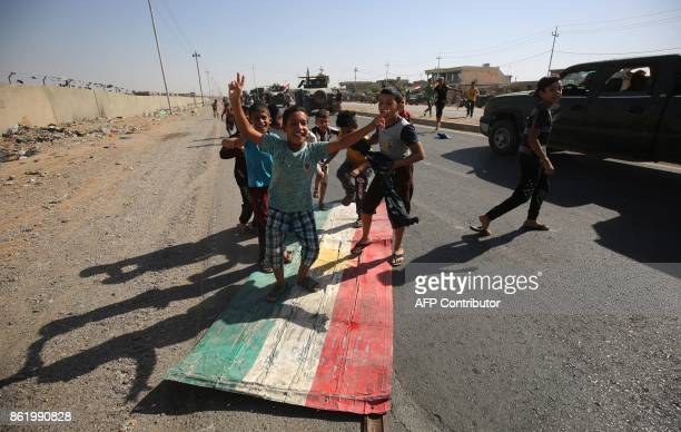 Iraqi children step on a Kurdish flag as forces advance towards the centre of Kirkuk during an operation against Kurdish fighters on October 16 2017...