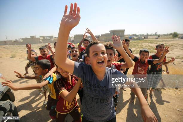 TOPSHOT Iraqi children wave to Iraqi forces as they arrive in the first neighbourhood on the southern outskirts of Kirkuk on October 16 2017 Iraqi...