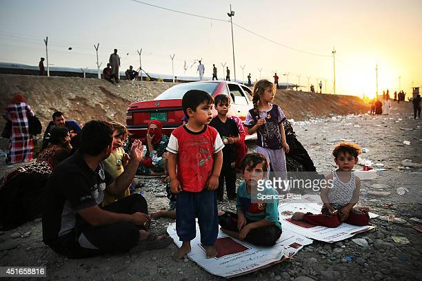 Iraqi children who fled recent fighting near the city of Mosul prepare to sleep on the ground with their family as they try to enter a temporary...