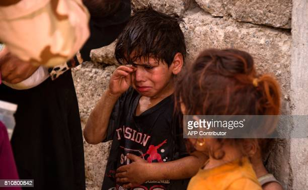 Iraqi children who fled the fighting between government forces and Islamic State group jihadists in the Old City of Mosul react as they stand by a...