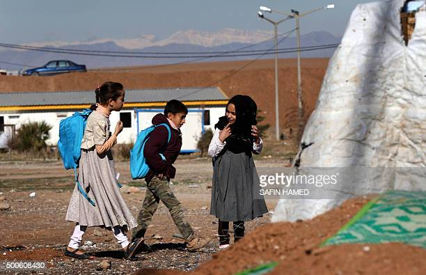 Iraqi children who fled the violence in the northern city of Tal Afar walk to school at the Bahrka camp for internally displaced people some ten...