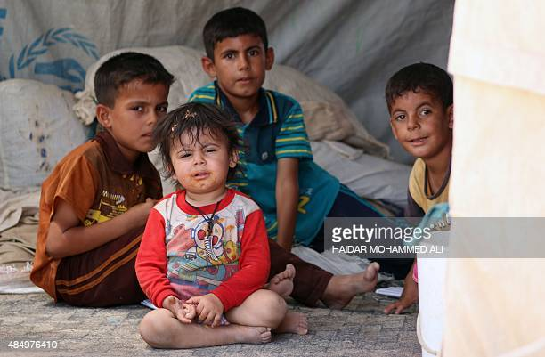 Iraqi children whose families fled violence in Iraq's Anbar province sit at a camp for displaced people in Baghdad's southern Dura district on August...