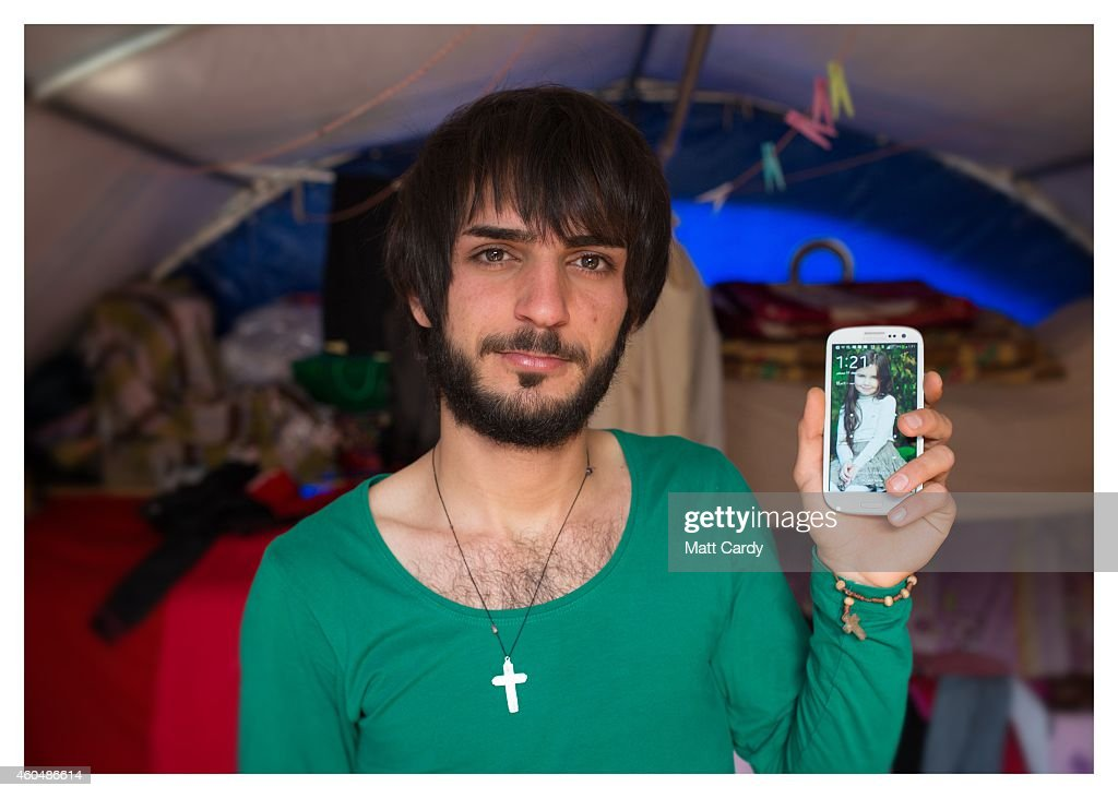Iraqi Christian Anas Khaleel poses for a photograph in his tented home erected in the grounds of Mazar Mar Eillia (Mar Elia) Catholic Church, that has now become home to hundreds of fellow Iraqi Christians who were forced to flee their homes - many with less than an hour to do so - as the Islamic State advanced earlier this year, on December 13, 2014 in Erbil, Iraq. Asked, after his family what was the one thing he could not leave behind as ISIL advanced on his home, the student and tiler from Qaraqosh said his Samsung smart phone. Although the autonomous Kurdistan region of Northern Iraq was already a refuge for an estimated 250,000 Syrian refugees, since the Islamic State began its onslaught on Iraq in June, Kurdistan has also taken in a more than one and a half million displaced people. Many have been placed in purpose-built refugee camps but the huge numbers mean thousands of others are forced to live in un-finished buildings or inadequate, makeshift shelters and as winter in the region closes in, there are growing concerns for the welfare of the refugees who, while their homes are still in ISIL controlled territory, have no realistic prospect of returning to them.