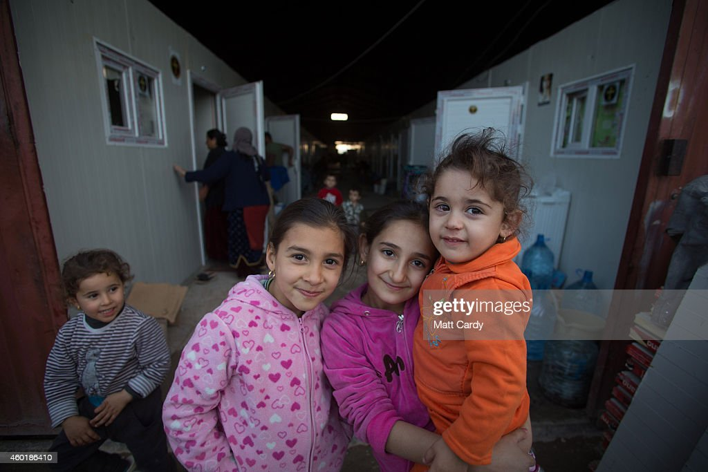 Iraqi Christian children, who fled from their homes because of Islamic State's advance earlier this year, pose for a photograph at the entrance to a warehouse that now contains temporary homes at a camp near Umm al-Nour Church, which is now home to hundreds of displaced Iraqi Christians on December 8, 2014 in Erbil, Iraq. Although the autonomous Kurdistan region in northern Iraq was already a refuge for an estimated 250,000 Syrian refugees, since the Islamic State began its onslaught on Iraq in June, Kurdistan has also taken in a more than one and a half million displaced people. Many have been placed in purpose-built refugee camps but the huge numbers mean thousands of others are forced to live in un-finished buildings or inadequate, makeshift shelters and as winter in the region closes in, there are growing concerns for the welfare of the refugees who, while their homes are still in ISIL controlled territory, have no realistic prospect of returning to them.