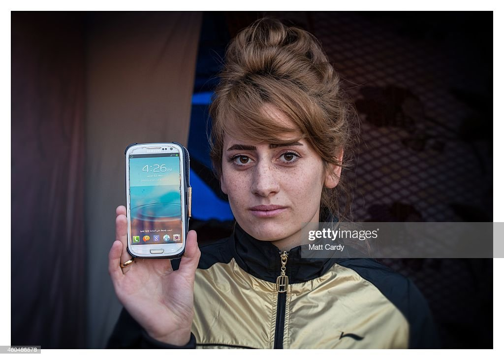 A Iraqi Christian, who asked not to be named, poses for a photograph in her tented home erected in the grounds of Mazar Mar Eillia (Mar Elia) Catholic Church, that has now become home to hundreds of fellow Iraqi Christians who were forced to flee their homes - many with less than an hour to do so - as the Islamic State advanced earlier this year, on December 13, 2014 in Erbil, Iraq. Asked, after her family what was the one thing she could not leave behind as ISIL advanced on her home, the student from Qaraqosh said her mobile phone. Although the autonomous Kurdistan region of Northern Iraq was already a refuge for an estimated 250,000 Syrian refugees, since the Islamic State began its onslaught on Iraq in June, Kurdistan has also taken in a more than one and a half million displaced people. Many have been placed in purpose-built refugee camps but the huge numbers mean thousands of others are forced to live in un-finished buildings or inadequate, makeshift shelters and as winter in the region closes in, there are growing concerns for the welfare of the refugees who, while their homes are still in ISIL controlled territory, have no realistic prospect of returning to them.