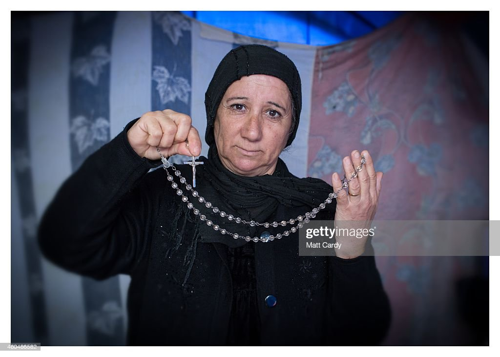 A Iraqi Christian, who asked not to named, poses for a photograph in her tented home erected in the grounds of Mazar Mar Eillia (Mar Elia) Catholic Church, that has now become home to hundreds of fellow Iraqi Christians who were forced to flee their homes - many with less than an hour to do so - as the Islamic State advanced earlier this year, on December 13, 2014 in Erbil, Iraq. Asked, after her family what was the one thing she could not leave behind as ISIL advanced on her home, the widowed housewife from Qaraqosh said her crucifix . Although the autonomous Kurdistan region of Northern Iraq was already a refuge for an estimated 250,000 Syrian refugees, since the Islamic State began its onslaught on Iraq in June, Kurdistan has also taken in a more than one and a half million displaced people. Many have been placed in purpose-built refugee camps but the huge numbers mean thousands of others are forced to live in un-finished buildings or inadequate, makeshift shelters and as winter in the region closes in, there are growing concerns for the welfare of the refugees who, while their homes are still in ISIL controlled territory, have no realistic prospect of returning to them.