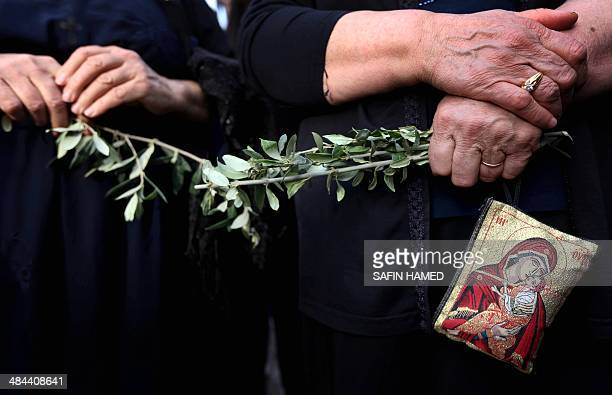 Iraqi Christian women hold a piece of olive branch as they gather at St Joseph church in Arbil the capital of the autonomous Kurdish region of...