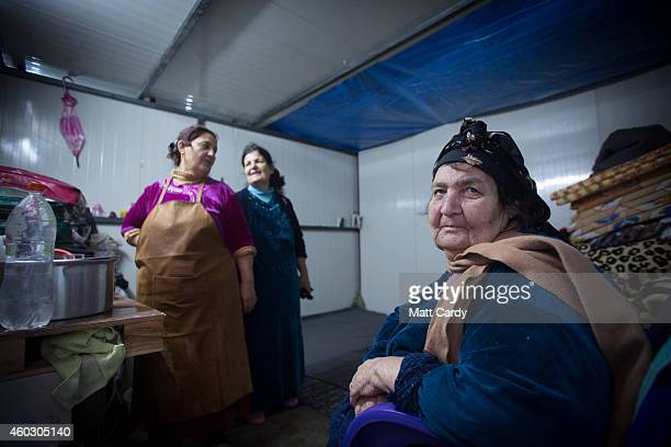 Iraqi Christian women who fled their homes as the Islamic State advanced earlier this year cook inside a shelter that has been installed inside an...