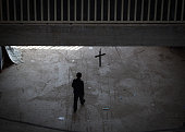 Iraqi Christians who fled from his home because of Islamic State's advance earlier this year walks beneath a cross erected inside the entrance hall...