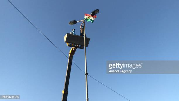 Iraqi citizens remove the Iraqi Kurdish Regional flag with a crane after Iraqi soldiers retook the control of the city center from Peshmerga forces...