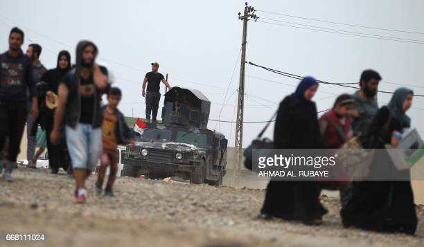 TOPSHOT Iraqi civilians flee the alAbar neighbourhood in west of Mosul as Iraqi forces battle against Islamic State group jihadist to recapture the...