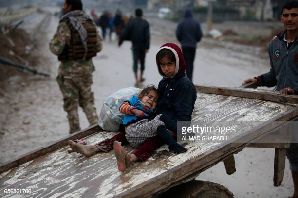 TOPSHOT Iraqi civilians flee the city of Mosul as Iraqi forces advance in their fighting against jihadists of the Islamic State group on March 23...
