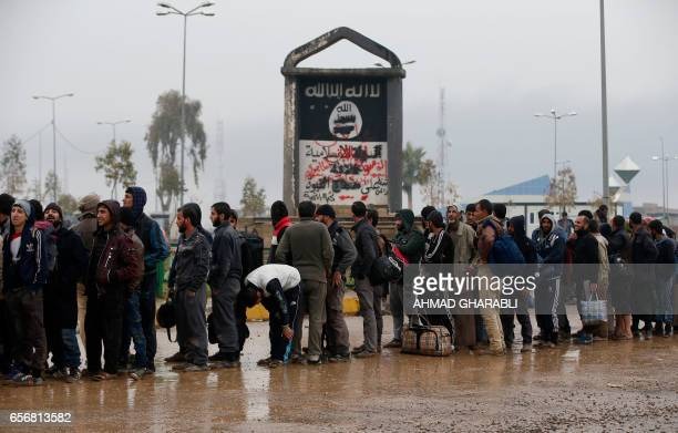 Iraqi civilians fleeing the city of Mosul gather in front of a sign by the the Islamic State group on March 23 2017 as Iraqi forces advance in their...