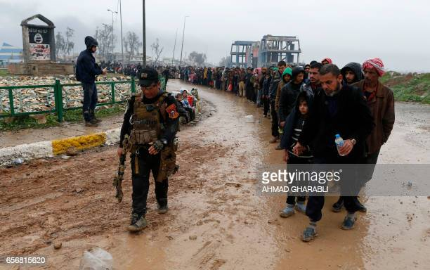 Iraqi civilians fleeing the city of Mosul walk past a sign by the the Islamic State group on March 23 2017 as Iraqi forces advance in their massive...