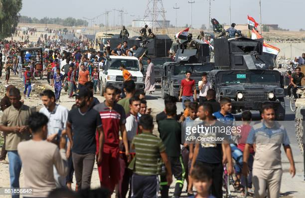 TOPSHOT Iraqi civilians gather as Iraqi forces arrive in the first neighbourhood on the southern outskirts of Kirkuk on October 16 2017 Iraqi forces...