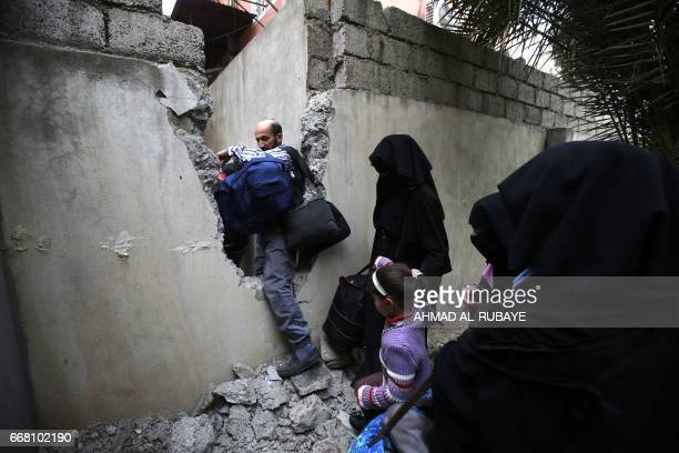 TOPSHOT Iraqi civilians pass through a safe passage in between houses as they flee the alAbar neighbourhood in west of Mosul while Iraqi forces...
