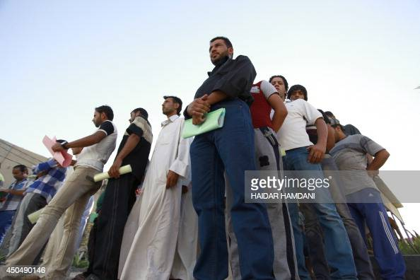 Iraqi civilians queue as they volunteer to join the fight against a major offensive by jihadists in northern Iraq on June 12 in the central Shiite...