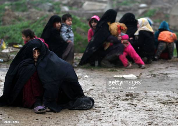 TOPSHOT Iraqi civilians sit on the road as they flee the city of Mosul while Iraqi forces advance in their massive operation to retake Iraq's second...