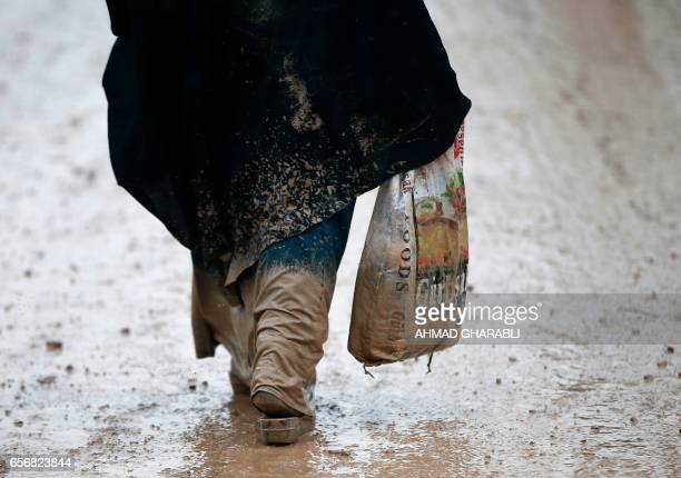 TOPSHOT Iraqi civilians walk in the mud as they flee the city of Mosul while Iraqi forces advance in their massive operation to retake Iraq's second...