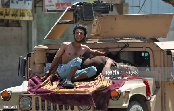 TOPSHOT Iraqi civilians who were injured in a suicide attack as people were escaping the Old City of Mosul sit on an Iraqi forces vehicle as they're...