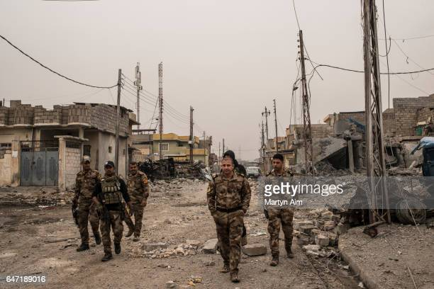 Iraqi Counter Terrorism Service officers of the Golden Division advance into the west Mosul district of alMamoun part of the offensive to retake the...