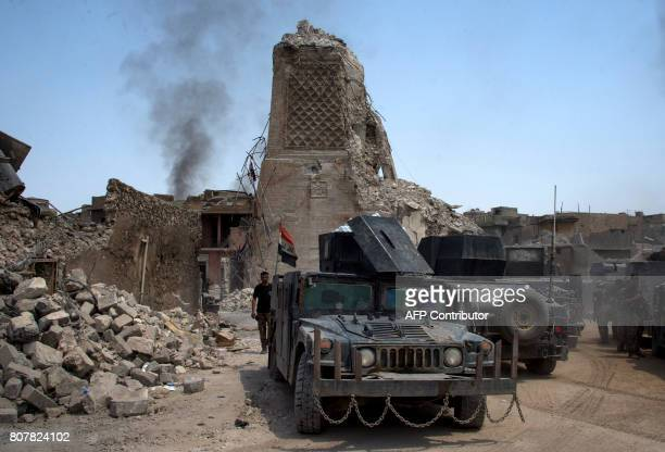 TOPSHOT Iraqi CounterTerrorism Service stand guard next to Mosul's destroyed ancient leaning minaret known as the 'Hadba' in the Old City of Mosul on...