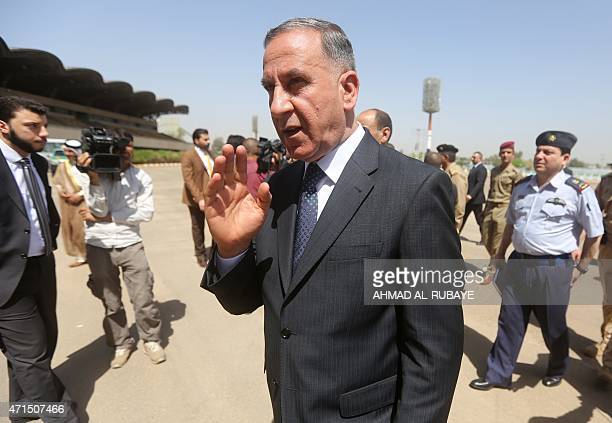 Iraqi Defense Minister Khaled alObeidi waves in Baghdad on April 29 during the funeral for the bodies of the victims believed to be massacred by...