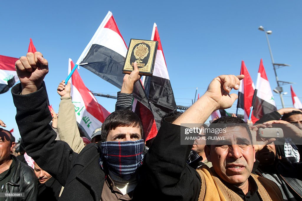 Iraqi demonstrators raise their fists during an anti-government protest outside the Sunni Umm al-Qura mosque in Baghdad on January 11, 2013. Thousands of Sunni Muslims took to the streets of Baghdad and other parts of Iraq to decry the alleged targeting of their minority, in rallies hardening opposition to the country's Shiite leader. AFP PHOTO/AHMAD AL-RUBAYE