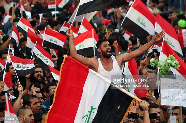 Iraqi demonstrators wave national flags during a demonstration to express support for Prime Minister Haider alAbadi's reform drive while calling on...
